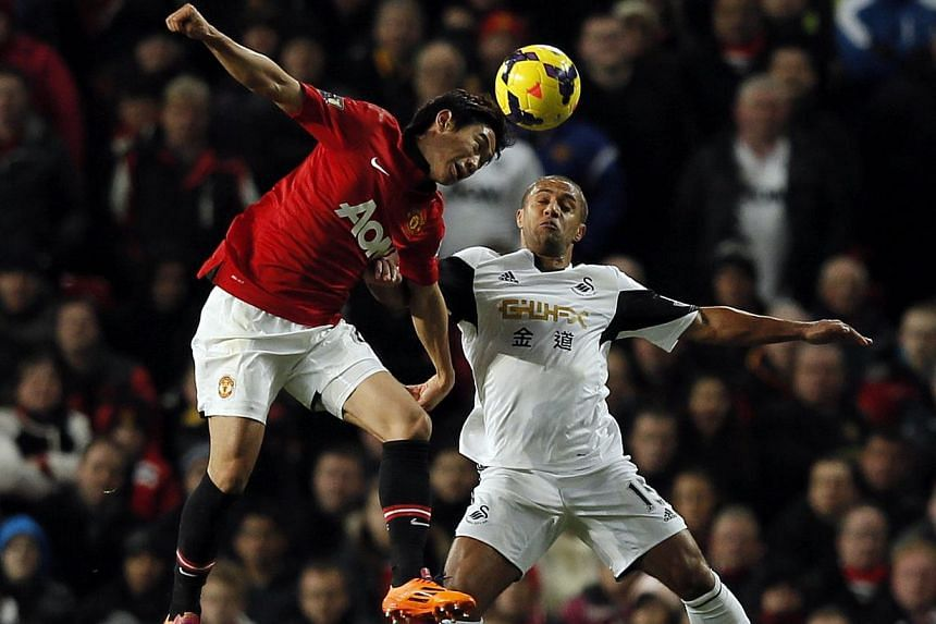 Swansea City's Wayne Routledge (right) challenges Manchester United's Shinji Kagawa during their English Premier League soccer match at Old Trafford in Manchester, northern England on Jan 11, 2014. -- PHOTO: REUTERS