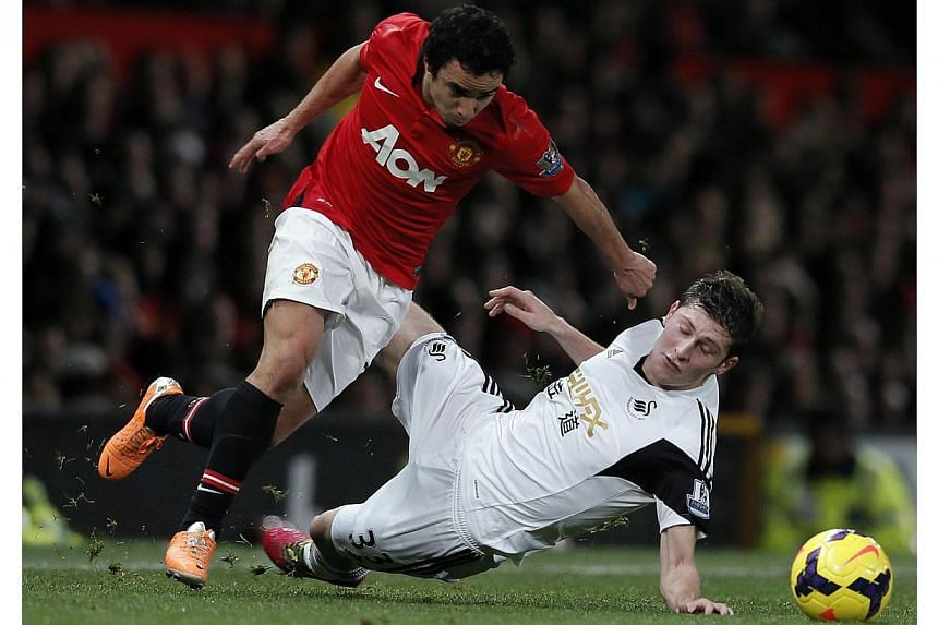 Swansea City's Ben Davies (right) challenges Manchester United's Rafael Da Silva during their English Premier League soccer match at Old Trafford in Manchester, northern England on Jan 11, 2014. -- PHOTO: REUTERS