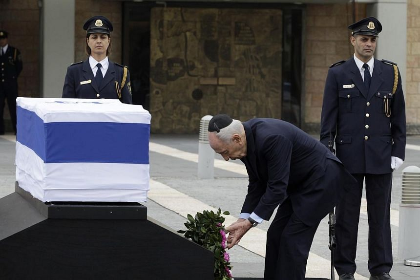 Israel's President Shimon Peres (centre) lays a wreath near the flag draped coffin of former Israeli prime minister Ariel Sharon as he lies in state at the Knesset, Israel's parliament, in Jerusalem, on Sunday, Jan 12, 2014.Sharon's body lay in