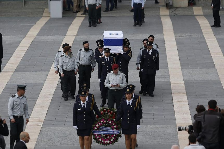 Israeli honour guards carry the coffin of former prime minister Ariel Sharon as it arrives at theKnesset, Israel's parliament, in Jerusalem, on Sunday, Jan 12, 2014. -- PHOTO: AFP