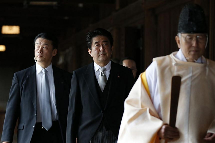 Japan's Prime Minister Shinzo Abe (centre) is led by a Shinto priest as he visits Yasukuni shrine in Tokyo, on Dec 26, 2013. North Korea on Sunday lashed out at Japan's hawkish prime minister for seeking to revise Tokyo's pacifist post-World War