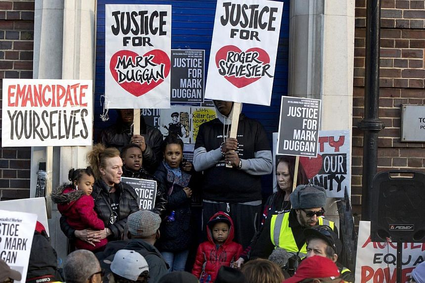 Family and supporters gather at a vigil for Mark Duggan, outside Tottenham Police Station in Tottenham, north London on Jan 11, 2014. Several hundred demonstrators rallied outside a London police station Saturday to condemn an inquest which found tha