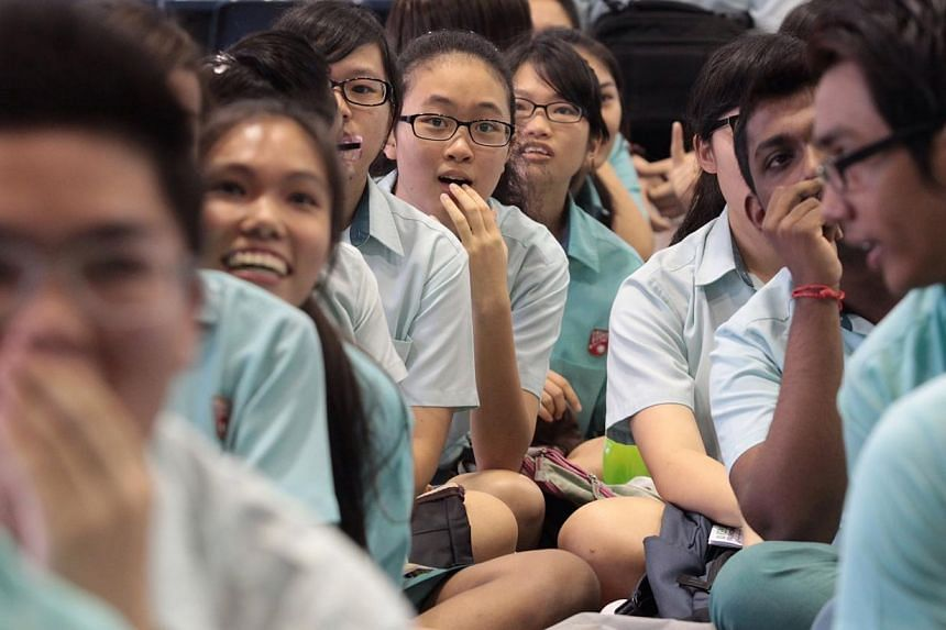 Si Ling Secondary School students react at their results projected on the screen in the school hall. -- ST PHOTO: NEO XIAOBIN