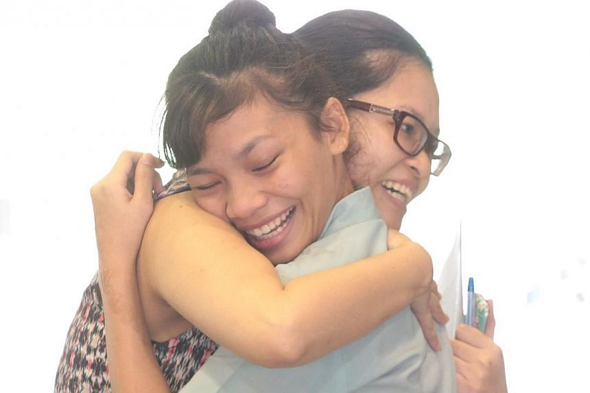 Hazleena Roslee (left) from Si Ling Secondary School is hugged by her combined humanities teacher Pearlyn Cheah, 30, after receiving her results. -- ST PHOTO: NEO XIAOBIN
