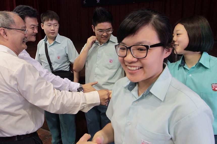 Si Ling Secondary School principal Mr Wong Lok Oon (extreme left) and vice-principal (admin) Mr Tan Tong Aik (second from left) congratulate students who did well for their GCE O-level examination results. -- ST PHOTO: NEO XIAOBIN