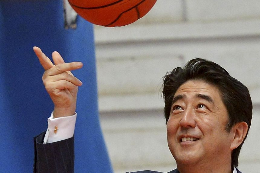 Japanese Prime Minister Shinzo Abe playing with a basketball after his meeting with the Mozambican women's basketball team members in Maputo on January 12, 2014. -- PHOTO: AFP