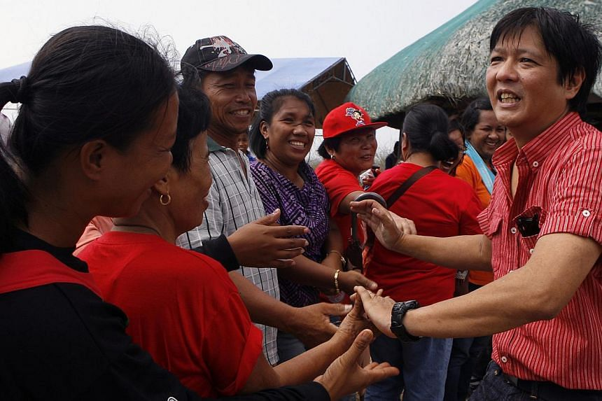 The Red Shirts: In this file picture dated April 6, 2010, congressman and senator candidate Ferdinand 'Bongbong' Marcos Jr (right), the only son of the late dictator Ferdinand Marcos, is greeted by supporters upon arrival at the Bangui town in Ilocos