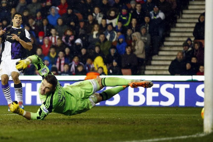 Liverpool's Luis Suarez (left) shoots and scores his second goal past Stoke City goalkeeper Jack Butland during their English Premier League soccer match at the Britannia stadium in Stoke-on-Trent, central England on Jan 12, 2014. Luis Suarez scored