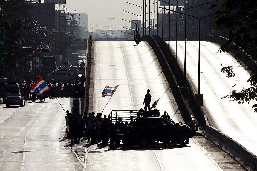 Anti-government protesters block a road in central Bangkok on January 13, 2014. -- PHOTO: REUTERS