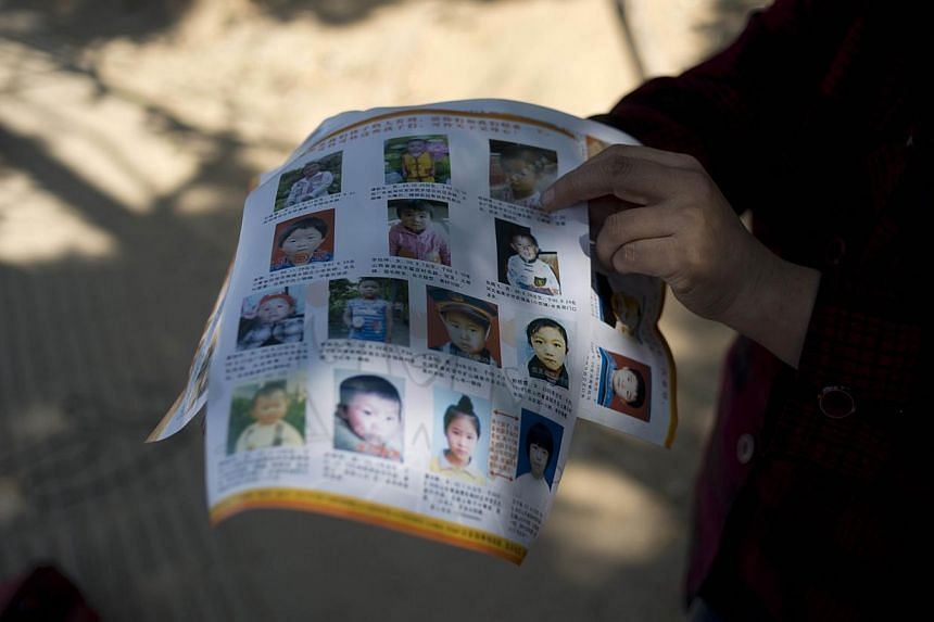 Ms Ye Jinxiu (right), 59, displaying pictures of missing children on the streets of Fuzhou on China's east coast Fujian province, helping other parents search for their children, devoting her failing health to what she knows is largely a lost ca