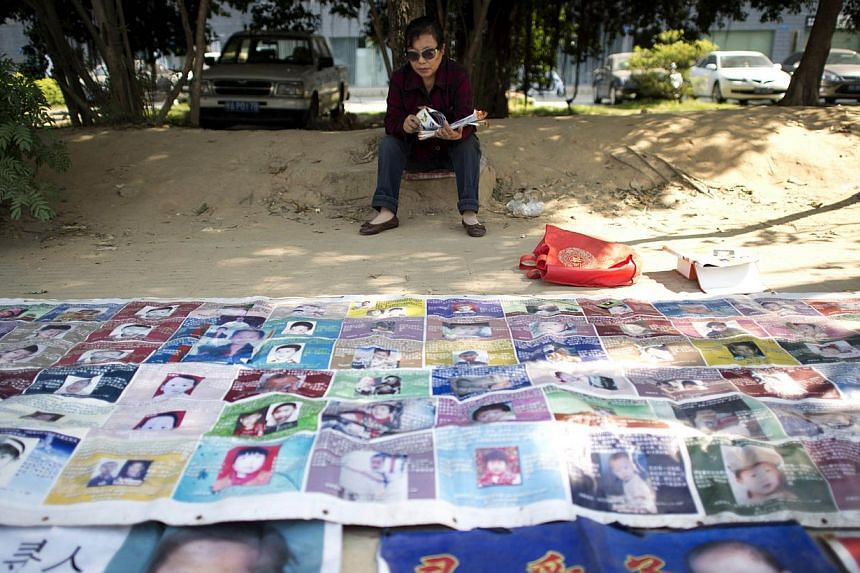 MsYe Jinxiu, 59, sitting before pictures of missing children on the streets of Fuzhou on China's east coast Fujian province, helping other parents search for their children, devoting her failing health to what she knows is largely a lost cause,
