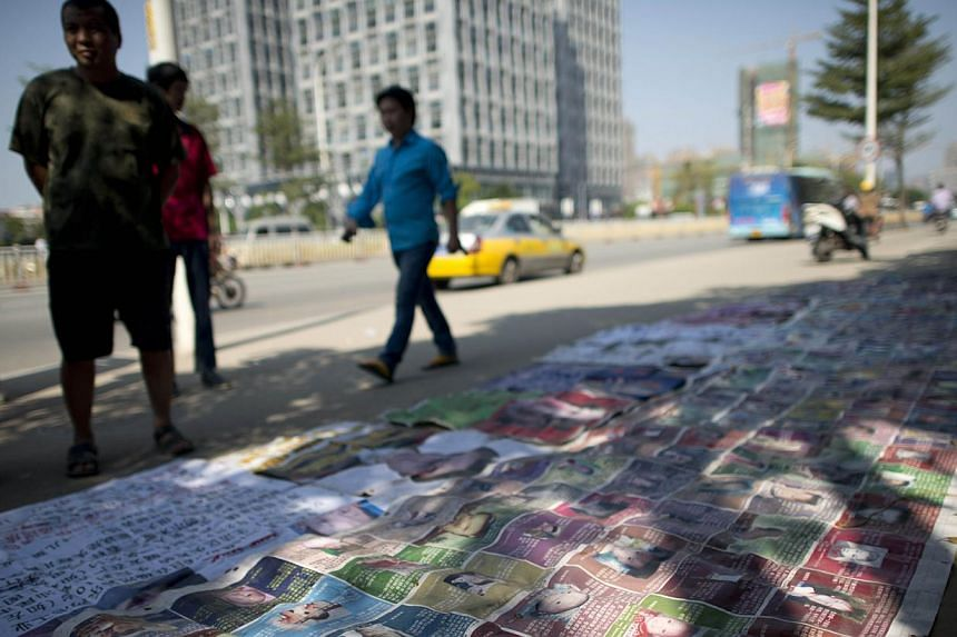 Passerbys stopping to look at the pictures of missing children displayed by Ms Ye Jinxiu (out of frame), on the streets of Fuzhou on China's east coast Fujian province, helping other parents search for their children, devoting her failing health to w