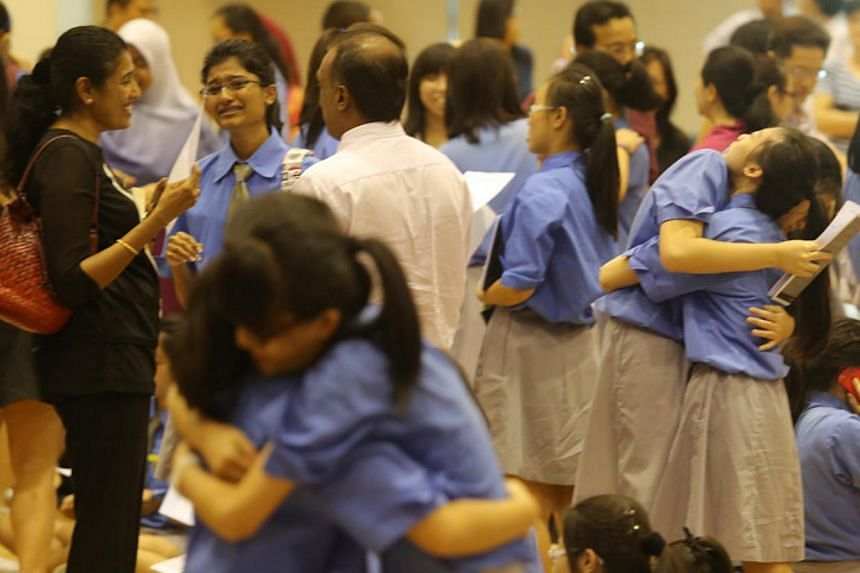 Students from Cedar Girls' Secondary School react upon hearing their O-level results, on Jan 13, 2014. Some 82.7 per cent of the students who took the GCE O-level examination last year achieved five or more passes - the highest in recent years.