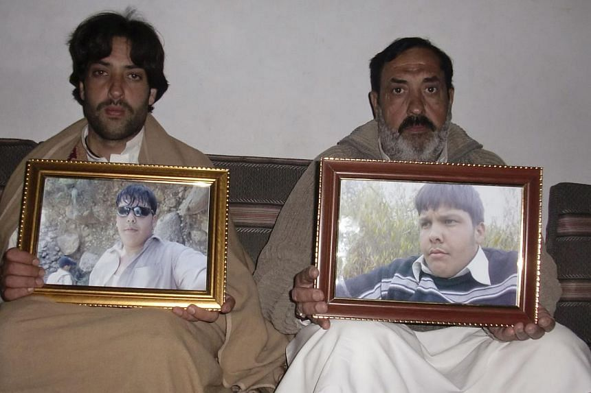 Mujahid Ali (right) and Mujtaba Hussan, the father and brother respectively of Aitezaz Hassan, who was killed in a suicide bomb attack, pose for the camera with framed pictures of Hassan at their residence in Hangu district, bordering North Wazirista