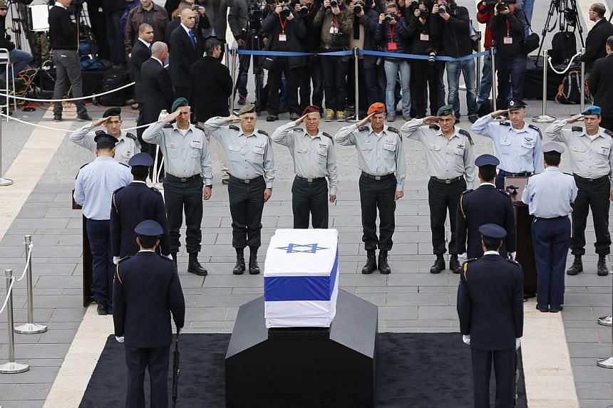Israeli army officers salute in front of the flag draped coffin of former Israeli prime minister Ariel Sharon as he lies in state before a memorial ceremony at the Knesset, Israel's parliament, in Jerusalem on Jan 12, 2014. A state memorial for the l