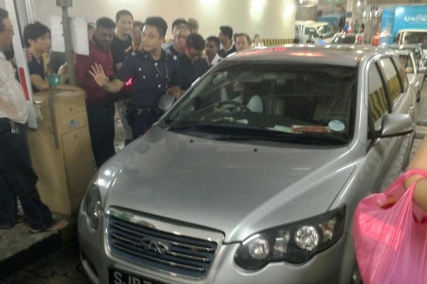 A woman got so upset when she encountered problems getting complimentary parking at the Lot One Shoppers' Mall that she refused to move when the barrier at the carpark was lifted, holding back other shoppers for close to one hour. -- PHOTO: MELVIN HO