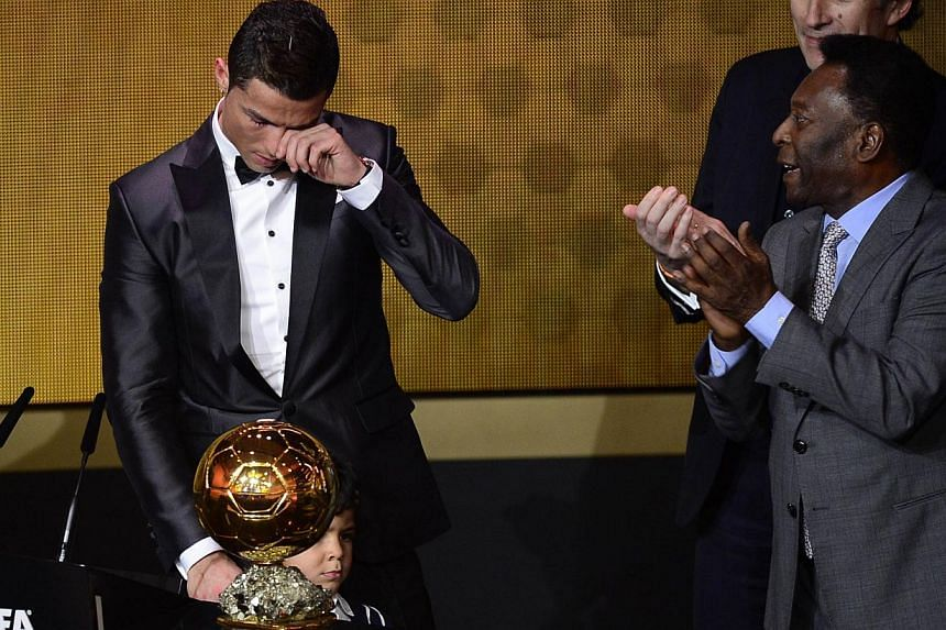 Real Madrid's Portuguese forward Cristiano Ronaldo cries after receiving the 2013 Fifa Ballon d'Or award for player of the year from Brazilian football legend Pele (right) and France Football president Francois Moriniere (back, right) during the Fifa