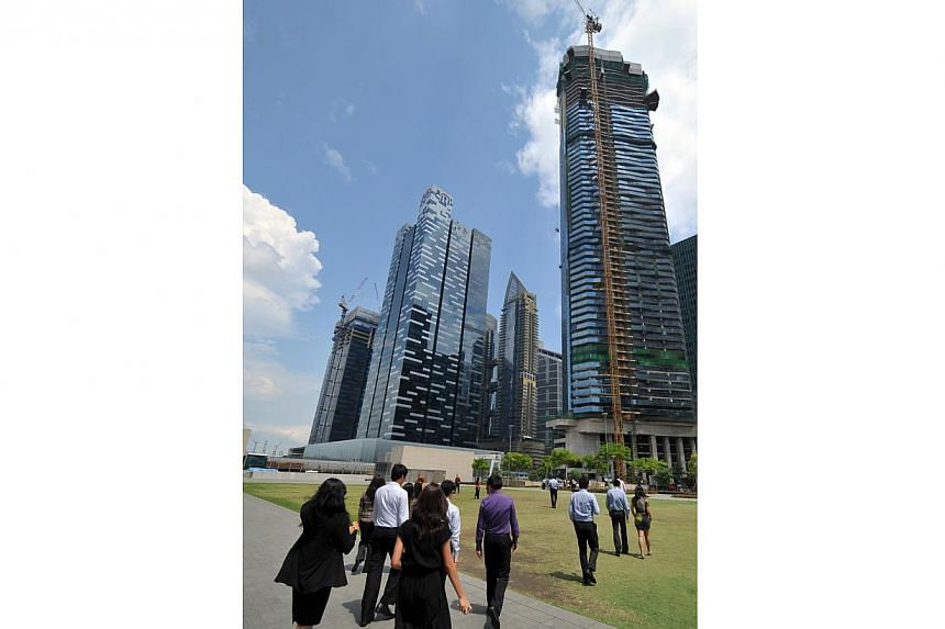 Office workers at the Marina Bay Financial Centre walk towards the nearly-completed Marina Bay Suites on May 17, 2012. The charred bodies of the two people who died at the Marina Bay Suites fire were discovered by SCDF fire fighters inside a service