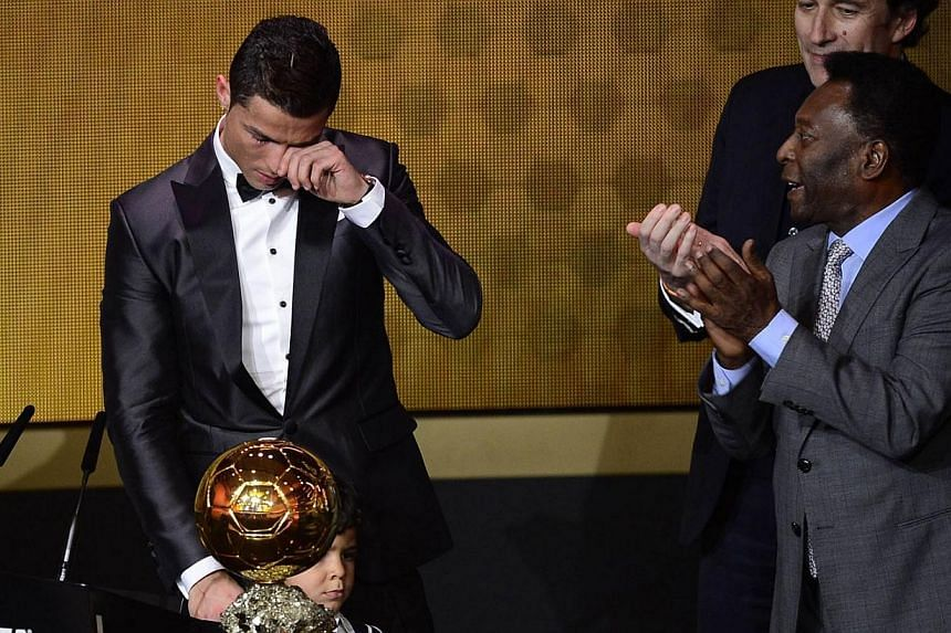 Real Madrid's Portuguese forward Cristiano Ronaldo (left) cries after receiving the 2013 Fifa Ballon d'Or award for player of the year from Brazilian football legend Pele (right) and France Football president Francois Moriniere (back, right) during t