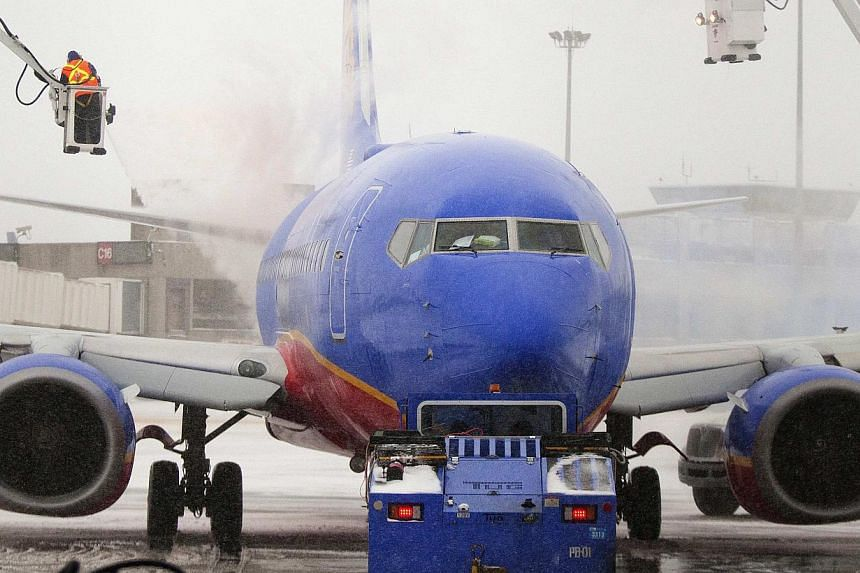 An ice crew sprays de-icing solution on a Southwest Airlines plane during a winter snow storm in Boston, Massachusetts, on Jan 2, 2014. Southwest Airlines on Jan 13, 2014, suspended two pilots from flying after their jetliner with 124 passengers land