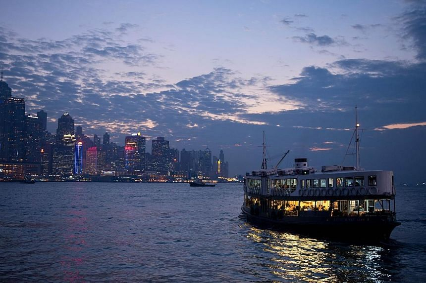 Commuters travel on the Star Ferry (right) in Victoria Harbour from Kowloon to Hong Kong island on Nov 21, 2013. Hong Kong on Tuesday retained the title of the world's freest economy for the twentieth year in a row, with rival Singapore closing