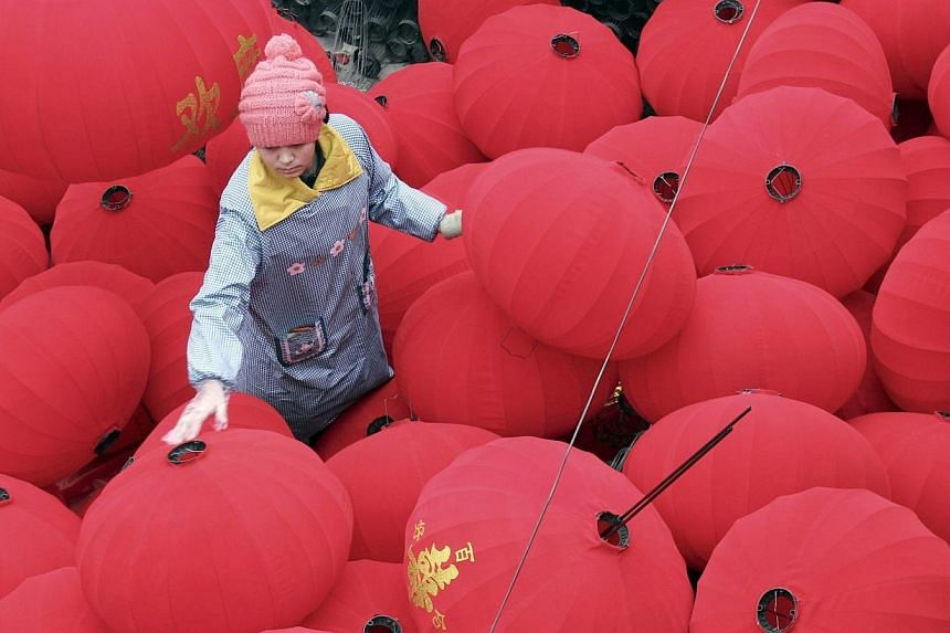 A worker walks among newly-made red lanterns as workers prepare for the sales boom ahead of the Spring Festival at a family workshop in Wenxian county, Henan province on Jan 7, 2014.A total of 3.6 billion trips are expected to be made during th