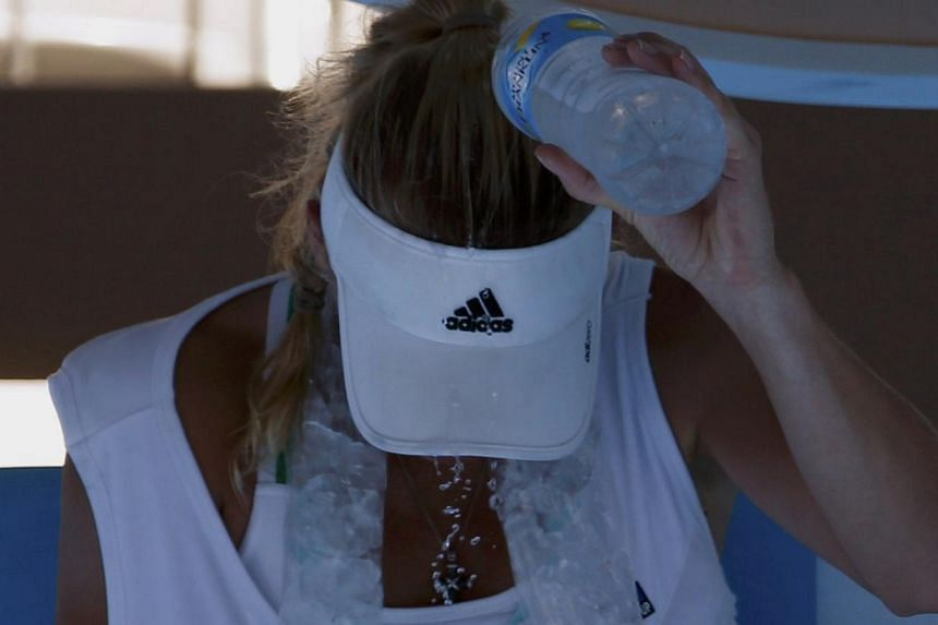 Caroline Wozniacki of Denmark pours water over her head during her women's singles match against Lourdes Dominguez Lino of Spain at the Australian Open 2014 tennis tournament in Melbourne on Jan 14, 2014. Top tennis stars were put through a punishing