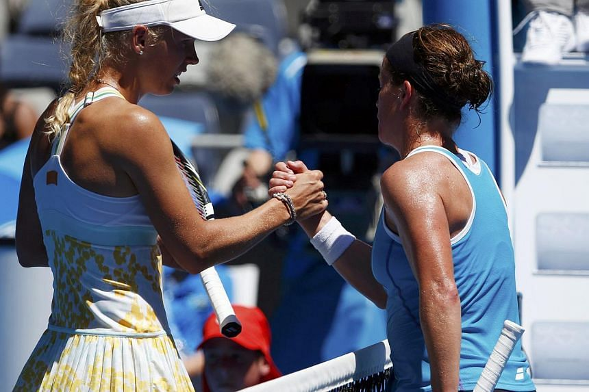 Caroline Wozniacki of Denmark shakes hands with Lourdes Dominguez Lino of Spain after winning their women's singles match at the Australian Open 2014 tennis tournament in Melbourne on Jan 14, 2014. Top tennis stars were put through a punishing workou