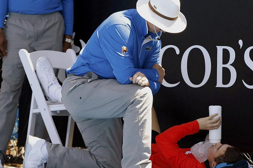 An official attends to a ball boy who collapsed during the men's singles match between Daniel Gimeno-Traver of Spain and Milos Raonic of Canada at the Australian Open 2014 tennis tournament in Melbourne on Jan 14, 2014. Top tennis stars were put thro