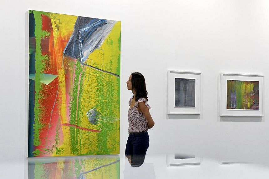 A visitor to Art Stage Singapore looks at German artist Gerhard Richter's 1982 oil on canvas painting from his coveted Abstrakte Bilder series. Priced at $14.45 million, it is the most expensive artwork at Art Stage. -- ST PHOTO: DESMOND FOO