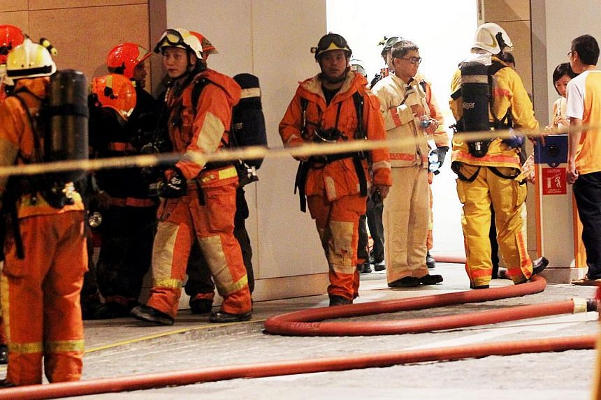 Firefighters at the Marina Bay Suites condominium after the blaze was put out. They took the fireman's lift to a safe level, before using the stairs to look for fire and for people to evacuate. On the 63rd floor, they met with intense heat and smoke,