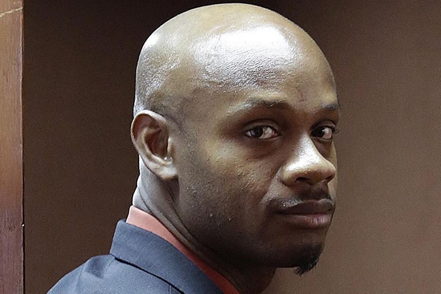 Jamaica's Olympic runner Asafa Powell, who tested positive for doping at the Jamaican Championships in 2013, returns to the conference room after being asked to step out during a presentation by attorneys on the first day of his hearing before the co