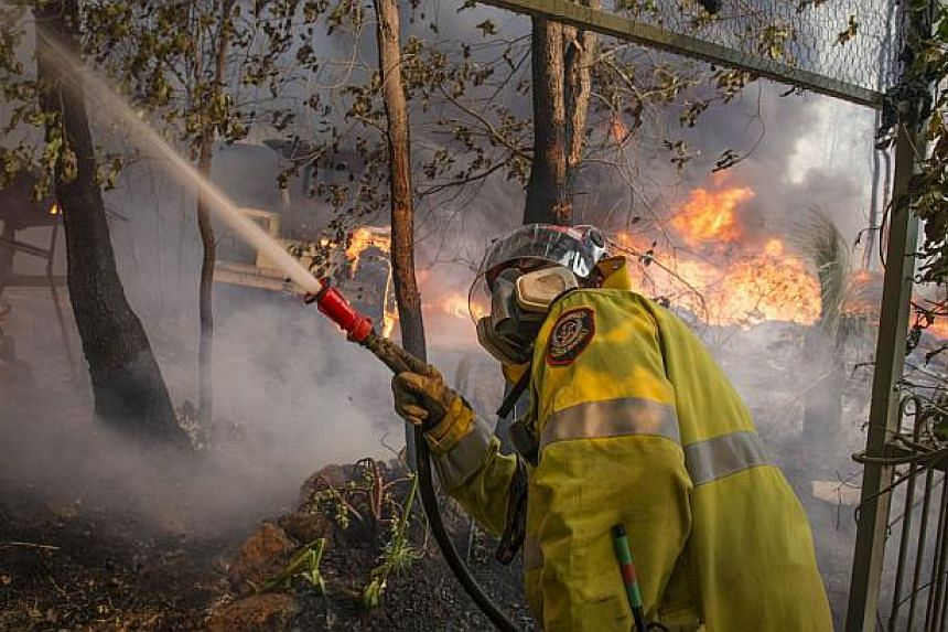This handout photo taken on Jan 12, 2014 and supplied by Australia's Department of Fire and Emergency Services (DFES) shows a firefighter working to contain wildfires in the Stoneville area, a suburb east of Perth in the state of Western Australia.&n