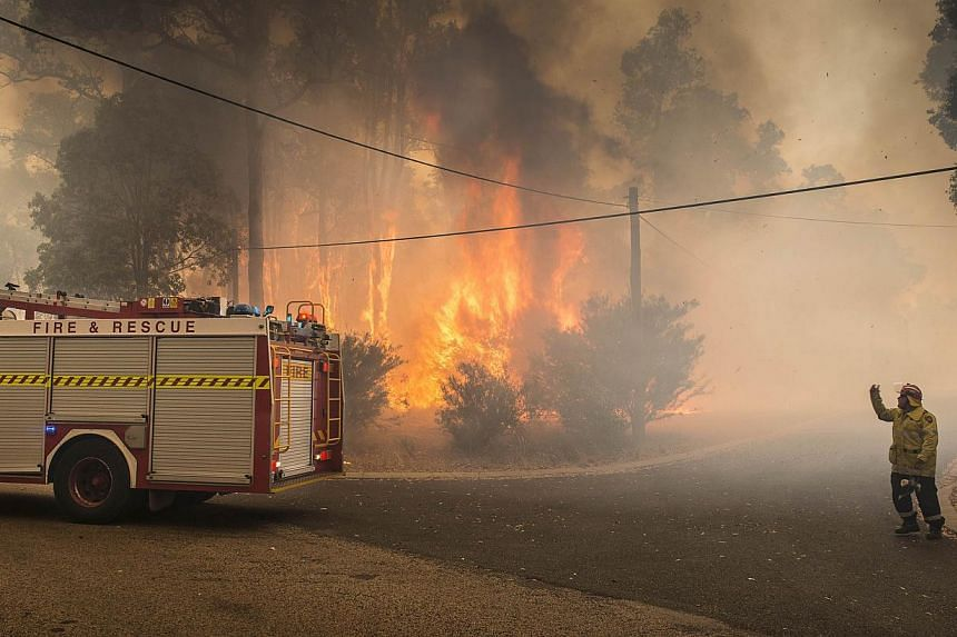 This handout photo taken on Jan 12, 2014 and supplied by Australia's Department of Fire and Emergency Services (DFES) shows firefighters working to contain wildfires in the Stoneville area, a suburb east of Perth in the state of Western Australia. --