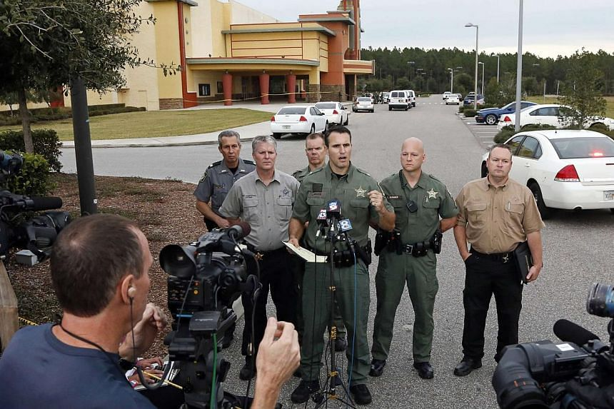 Pasco County Sheriff Chris Nocco (centre) speaks to the media as police tape surrounds the Cobb Grove 16 movie theatre in Wesley Chapel, Florida, on Jan 13, 2014. -- PHOTO: REUTERS