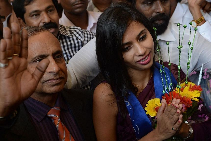 Indian diplomat Devyani Khobragade (right), accompanied by her father Uttam Khobragade, gives a traditional greeting on her arrival at the domestic airport in Mumbai on Jan 14, 2014. Senior United States and Indian diplomats met in Washington to disc