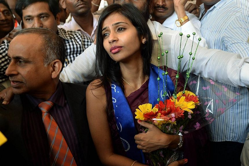 Indian diplomat Devyani Khobragade (right), accompanied by her father Uttam Khobragade, arrives at the domestic airport in Mumbai on Jan 14, 2014. A lawyer for Indian diplomat Devyani Khobragade on Tuesday asked a United States (US) judge to throw ou