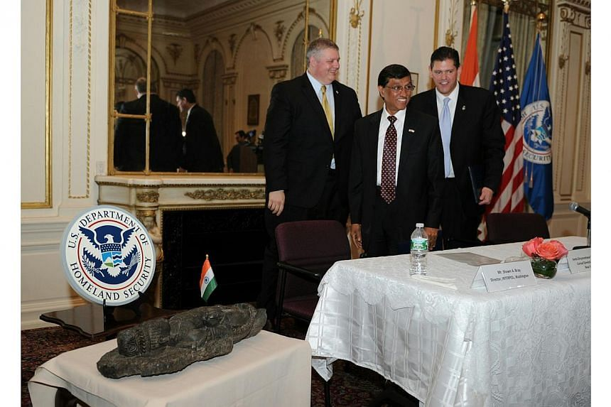 Interpol's Washington director Shawn Bray (left), India's Consul General Dnyaneshwar Muluy (centre) and Homeland Security executive James Dinkins smile after a repatriation ceremony on Jan 14, 2014 at the Consulate General of India in New York. -- PH
