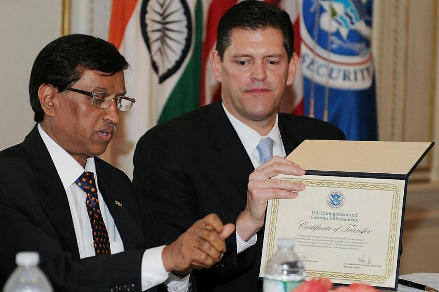 India's Consul General Dnyaneshwar Muluy (left) and Homeland Security executive James Dinkins during a repatriation ceremony Jan 14, 2014 at the Consulate General of India in New York. -- PHOTO: AFP