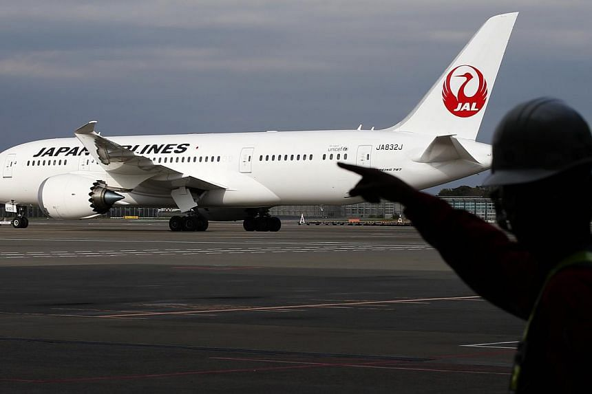 A staff of Japan Airlines' (JAL) walks past one of the company's Boeing Co's 787 Dreamliner plane at Narita international airport in Narita, east of Tokyo, on Nov 11, 2013.Japan Airlines Co Ltd said it temporarily grounded one of its Boeing 787
