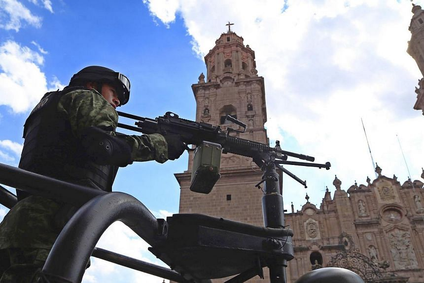 A member of the Mexican army patrolling the streets surrounding the cathedral in Morelia, Mexico during a ceremony in which Mexican Interior Secretary Miguel Angel Osorio Chong signed an agreement to stop violence in the state on Jan 13, 2014. But de