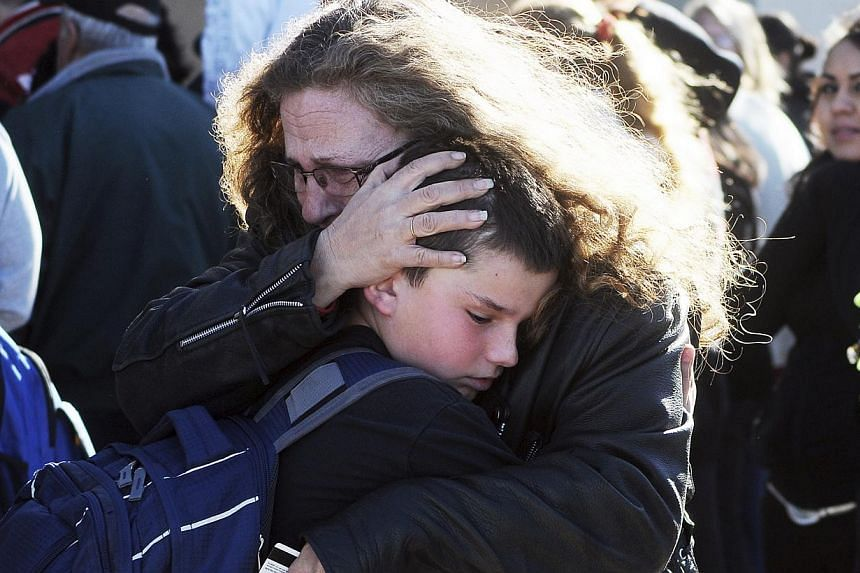 Students are reunited with families at a staging ground set up at the Roswell Mall following an early morning shooting at Berrendo Middle School in Roswell, New Mexico, on Jan 14, 2014. -- PHOTO: REUTERS