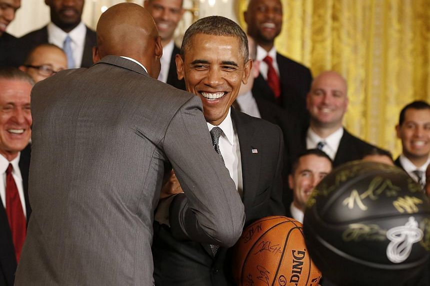 U.S. President Barack Obama smiles as he holds a basketball given to him as he hosts the 2013 NBA champions Miami Heat in the East Room of the White House in Washington, on Jan 14, 2014. Congress is prepared to allow United States (US) President Bara