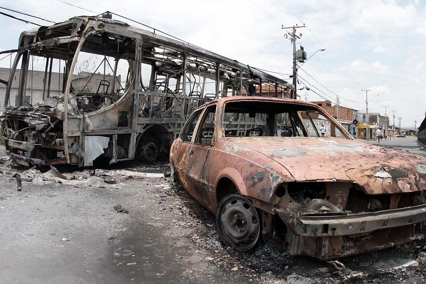 View of a burnt bus and car at Vida Nova bus station, in Campinas, some 96 km from Sao Paulo, Brazil on Jan 13, 2013.A Brazilian police commander said on Tuesday that there was strong evidence that fellow officers may have been involved in a sp