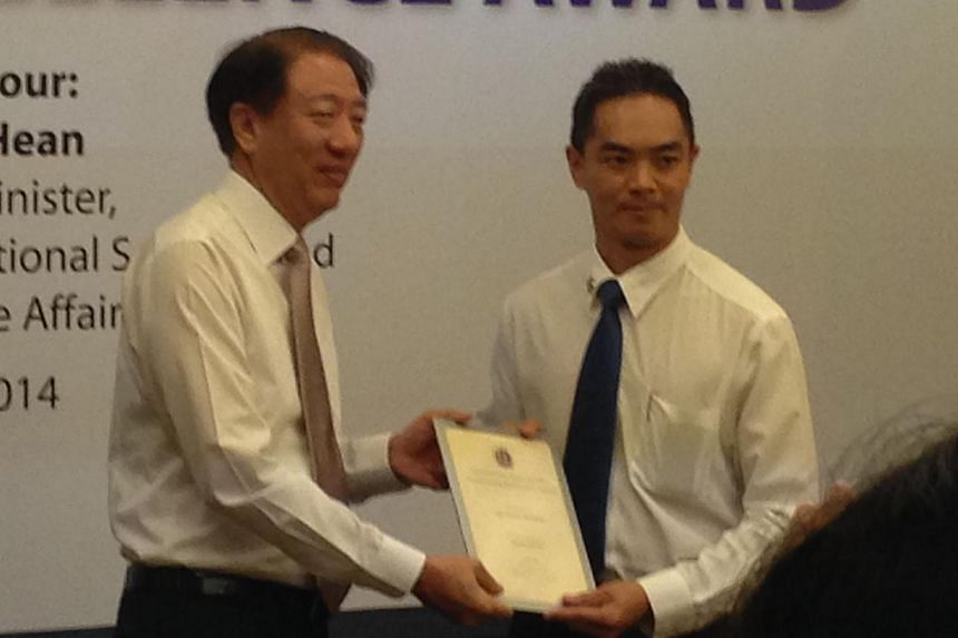 Mr Teo presenting the Operational Excellence Award to DAC Adrian Quek, Assistant Director Major Crime Division, CID.-- ST PHOTO: YEO SAM JO