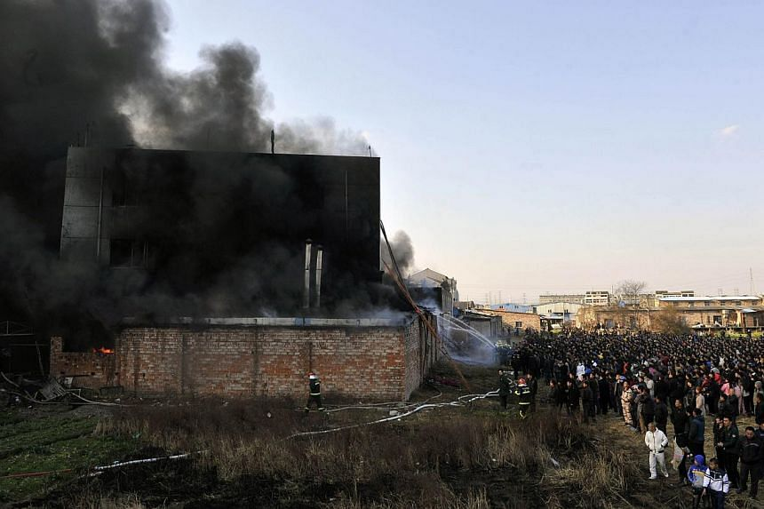 Firefighters battling a blaze at the Dadong Shoes factory in Taizhou, Zhejiang province, on Jan 14, 2014. The fire killed 16 people and injured five, state media reported, the latest disaster to highlight China's poor workplace safety record. -- PHOT