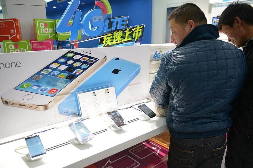 This picture taken on Jan 14, 2014, shows customers looking at Apple iPhones in a China Mobile store in Shanghai.The world's biggest mobile network is ready to offer Apple's iPhone, but while the US technology giant has declared China its bigge