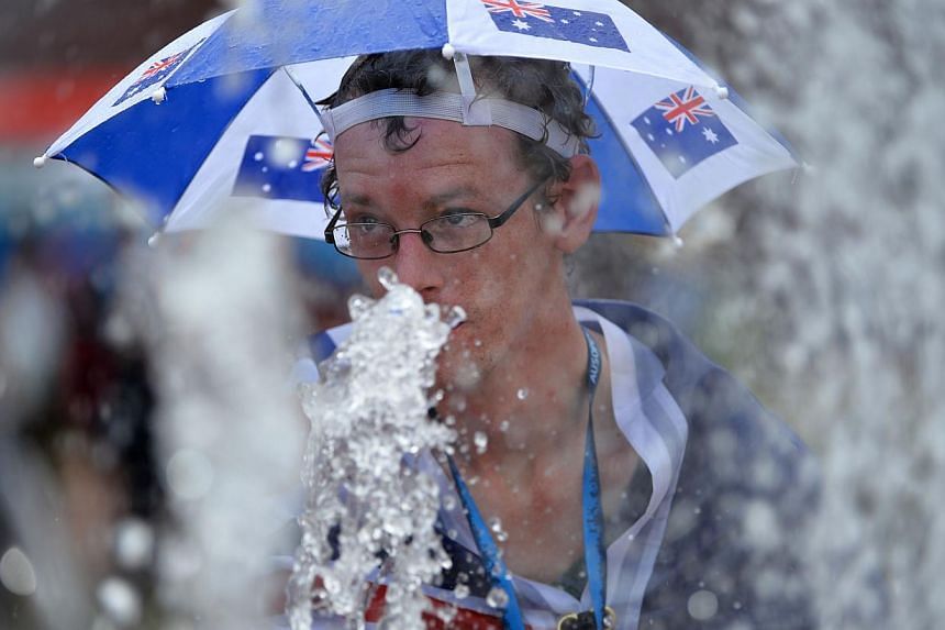 A man seeks relief from the heat during second round action on day three of the 2014 Australian Open tennis tournament in Melbourne on Jan 15, 2014. -- PHOTO: AFP