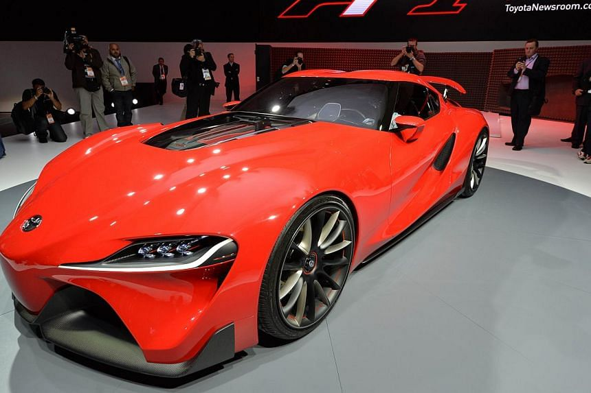Members of the media get a look at the Toyota FT-1 concept car during a press preview at the North American International Auto Show on Jan 13, 2014 in Detroit, Michigan. Asian rivals Toyota Motor Corp and Kia Motors unveiled concept sports cars