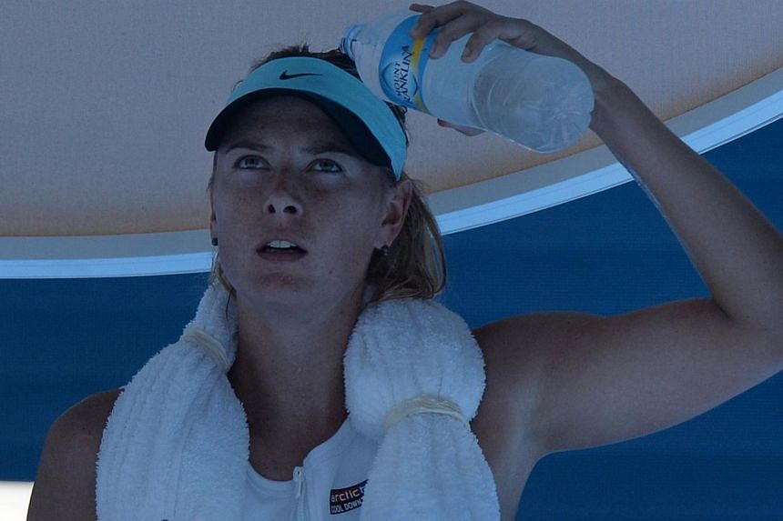Russia's Maria Sharapova cools off by pouring water over her head during her women's singles match against Karin Knapp of Italy at the Australian Open 2014 tennis tournament in Melbourne on Thursday, Jan 16, 2014. -- PHOTO: AFP